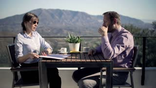 Young businessman signing documents sitting by table with his coworker at terrace in the country