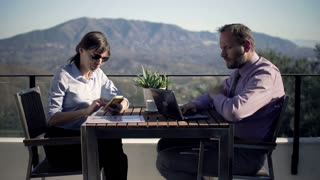 Young business couple working with smartphone and laptop by table at home