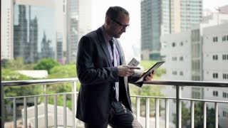 Businessman comparing data on smartphone and tablet computer on terrace with skyscraper view