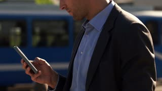 Businessman hands texting on smartphone in the city