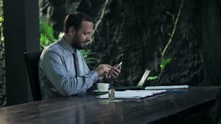 Businessman with smartphone drinking coffee at home at night