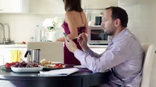 Businessman with smartphone sitting in the kitchen, his wife bring coffee