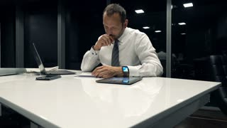 Businessman writing notes in documents sitting by table at the office during night, 4K