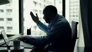 Angry businessman talking on cellphone by desk at office