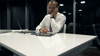 Bored businessman sitting by desk in office by night, 4K