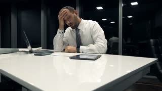 Sad, overwhelmed businessman with documents and tablet computer by table in the office during night, 4K