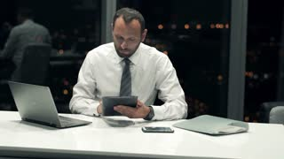 Young businessman working on modern tablet, laptop and smartphone in the office during night