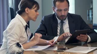 businesspeople comparing data on tablet and documents by table in the office