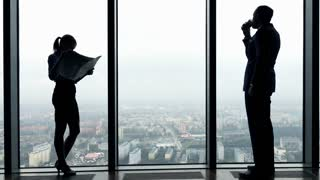 Silhouette of young businesspeople reading newspaper and drinking coffee by the window in the office, 4K