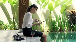 Businesswoman comparing data on tablet computer and smartphone sitting on the edge of swimming pool
