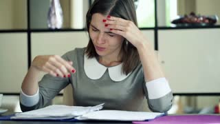 Businesswoman having headache during working with documents in the office