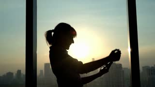 Successful businesswoman with smartphone standing by window in office during sunset, 240fps