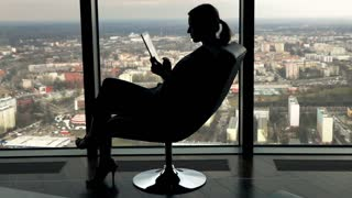 Silhouette of young businesswoman working on tablet computer sitting by armchair by the window in the office, 240fps