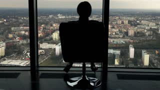 Silhouette of happy businesswoman touring round on the armchair in the office, super slow motion