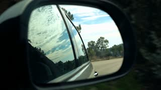 Car mirror driving in the country mountains, super slow motion