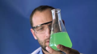 Chemist mixing chemicals in erlenmeyer flask, super slow motion, shot at 240fps