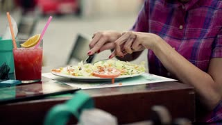 Closeup of tasty salad being eaten with fork and knife