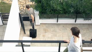 Couple break up, man going away with suitcase, super slow motion
