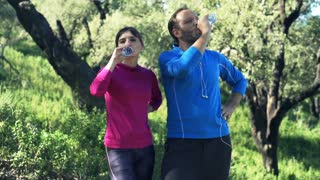 Couple drinking water after jogging in the forest,super slow motion