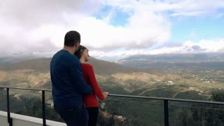 Couple hugging and enjoying view from terrace in country mountains, super slow motion
