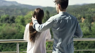 Couple in love kiss, hug, and drink juice on terrace with great view, super motion, shot at 240fps