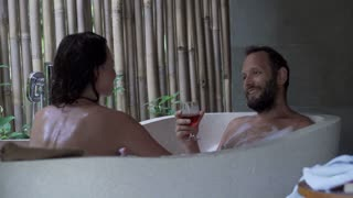 Couple in love kissing talking, and drinking wine during bath at home