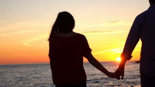 Couple standing on beach and admire sunset, slow motion shot at 240fps