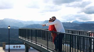 Couple talking and admire view standing on terrace in the city with mountains view, 240fps