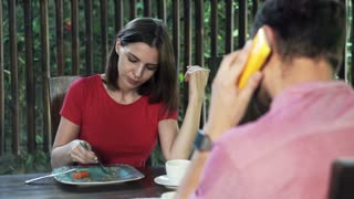 Couple talking on cellphone, drinking and eat by table at home