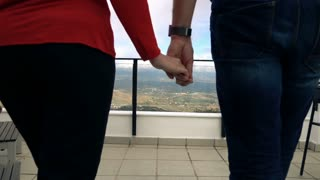 Couple walking and holding hands on terrace, super slow motion