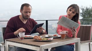 Young couple with tablet newspaper sitting during breakfast on terrace