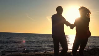 Young happy couple turning round on beach during sunset, super slow motion