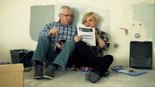 Overwhelmed mature couple counting bills with smartphone sitting on floor at their new home