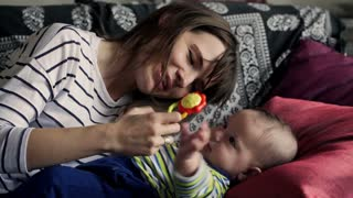 Cute, funny small baby playing with toy with his mother