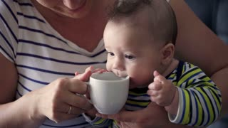 Cute small baby sitting on the mother's knees and playing with mug
