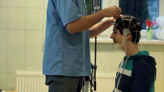 Doctor preparing kid for brain scan in hospital