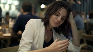 Drunk, sad woman drinking beer while sitting in the bar, 4K