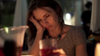 Drunk, sad woman drinking wine while sitting in cafe at night