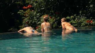 EDITORIAL Girlfriends relaxing on the edge of swimming pool, super slow motion