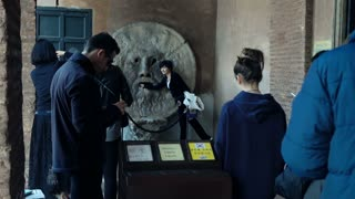 Woman posing to the photo while putting her hand into the mouth of truth in Rome - EDITORIAL