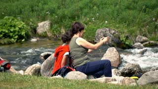 Editorial: Two women taking photo with cellphone in forest stream, slow motion 240fps