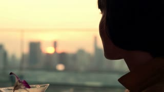 Face of beautiful woman drinking cocktail on terrace during sunset