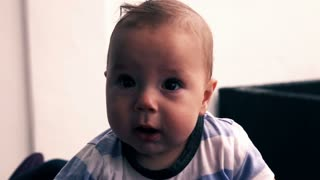 Face of cute surprised little baby boy, super slow motion
