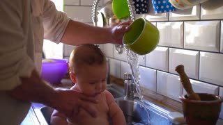 Father washing his child in the kitchen sink, super slow motion