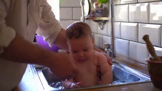 Father washing his child in the kitchen sink