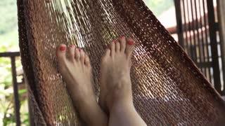 Female feet lying on hammock on terrace, slow motion, shot at 120fps