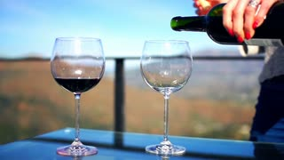 Female hands pouring wine on the terrace in the country, super slow motion