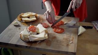 Female hands preparing sandwich for breakfast on wooden table