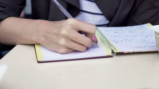 Female hands writing notes in notebook  on the table