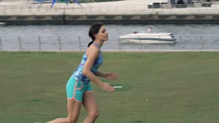 Female jogger runs in the city close to the river, super slow motion, 120fps